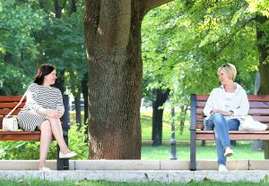 women on benches in conversation to demonstrate intimacy in trust fundraising