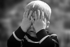 child hiding behind their hands