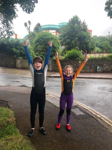 two kids in wetsuits cheering