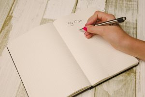 hand writing a plan into a journal